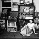 Norma with radio, record player, and reel-to-reel tape collection. Oakland, California c.1954-55.